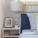 Lampada bianca moderna sulla tavola con i cuscini sul letto immagini stock libere da diritti