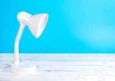 Lampada bianca sullo scrittorio di legno bianco, fondo blu Immagine Stock