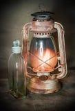 Lampada bruciante arrugginita e una bottiglia di cherosene Immagini Stock