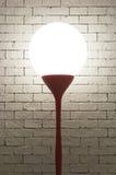 Lampada con forma del cerchio sul verticale bianco del fondo dei mattoni Immagine Stock