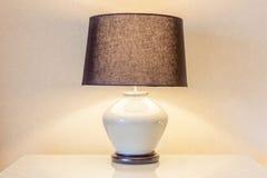 Lampada da tavolo e la sua ombra sulla carta da parati nella camera da letto Fotografia Stock