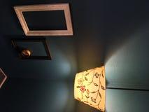 Lampada del fiore di Lit nell'angolo con le cornici vuote sulla parete con un portacenere in una di loro fotografia stock
