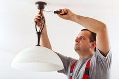 Lampada del soffitto del montaggio dell'elettricista Fotografie Stock