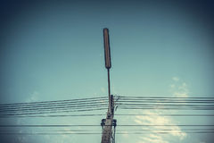 Lampada dell'iluminazione pubblica con il palo di potere ad alta tensione e cavi aggrovigliati Fotografia Stock Libera da Diritti