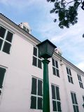 lampada di via classica e la vecchia costruzione bianca immagine stock