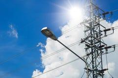 Lampada di via con il palo ad alta tensione di elettricità sul cielo blu di giorno soleggiato Fotografia Stock