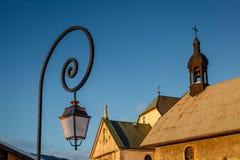 Lampada di via e chiesa medievale in Megeve Fotografie Stock