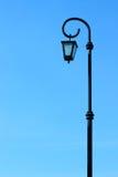 Lampada di via nera alta sul cielo blu del fondo Fotografia Stock Libera da Diritti