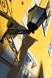 Lampada di via su una parete gialla con le finestre Fotografia Stock