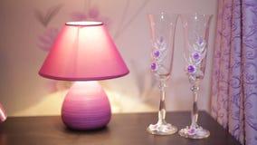 Lampada e due vetri sulla tavola nella camera da letto video d archivio