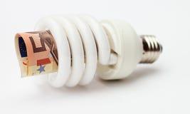 Lampada economizzatrice d'energia con la banconota Fotografie Stock