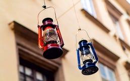 Lampada-lanterne autentiche di attaccatura rossa e blu sui precedenti delle finestre della costruzione, concetto degli oggetti au fotografia stock libera da diritti