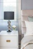 Lampada nera dal lato di legno bianco della tavola in camera da letto Fotografie Stock