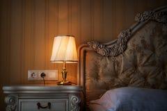 Lampada su un comodino accanto ad un letto Immagini Stock