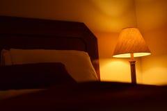 Lampada tenue di notte (traversina leggera) accanto ad un letto comodo Immagine Stock Libera da Diritti