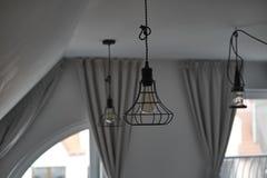 Lampade di pendente industriali del cavo in un salone del sottotetto Immagine Stock Libera da Diritti