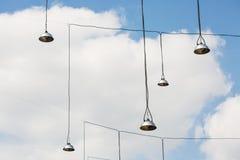 Lampade di via che appendono sui cavi lunghi contro il fondo del cielo Fotografia Stock Libera da Diritti