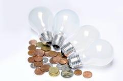 Lampade incandescenti e monete Immagini Stock