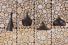 Lampade nere in un caffè che appende su un fondo delle cabine di ceppo di legno sulla parete immagini stock libere da diritti