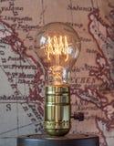 Lampadina classica di edison con il filamento di ciclaggio del carbonio sulle sedere della mappa fotografia stock libera da diritti