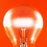Lampadina d'ardore su colore rosso Fotografia Stock
