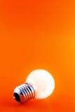 Lampadina d'ardore su colore rosso Fotografia Stock Libera da Diritti