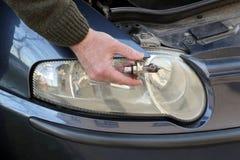 Lampadina dell'automobile rotta H4 in mano del meccanico Immagine Stock Libera da Diritti