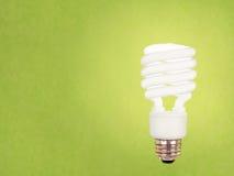 Lampadina di CFL su verde Immagini Stock Libere da Diritti