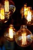 Lampadina di Edison che appende su un cavo lungo Luce gialla calda accogliente retro Fotografie Stock