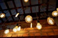 Lampadina di Edison che appende su un cavo lungo Luce gialla calda accogliente retro Fotografia Stock
