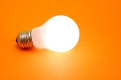 Lampadina di Lit su priorità bassa arancione Fotografia Stock Libera da Diritti