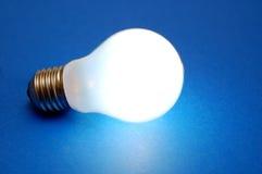 Lampadina di Lit su priorità bassa blu Fotografia Stock Libera da Diritti