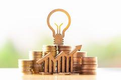 Lampadina e pila di monete nel concetto del risparmio e di crescita dei soldi o dei risparmi di energia immagini stock
