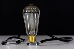 Lampadina e stetoscopio Fotografia Stock