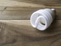 Lampadina economizzatrice d'energia su fondo di legno Fotografia Stock