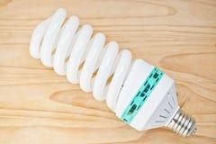Lampadina economizzatrice d'energia su legno duro Fotografia Stock
