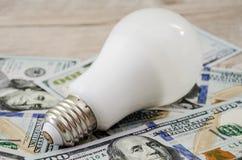 Lampadina economizzatrice d'energia sui dollari fotografie stock
