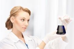 Lampadina femminile della tenuta del chimico con i prodotti chimici Immagine Stock