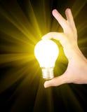 Lampadina incandescente gialla luminosa a disposizione fotografia stock