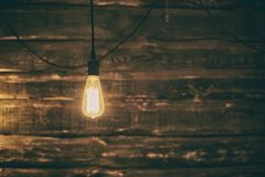 Lampadina leggera di Edison su fondo di legno scuro immagine stock