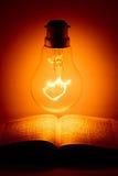 Lampadina sopra la bibbia santa Fotografia Stock Libera da Diritti