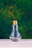 Lampadina su superficie di legno con gli ambiti di provenienza verdi Fotografia Stock
