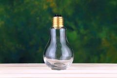 Lampadina su superficie di legno con gli ambiti di provenienza verdi Fotografie Stock Libere da Diritti