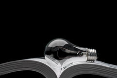 Lampadina su un libro che mostra le idee da ispirazione Fotografia Stock Libera da Diritti