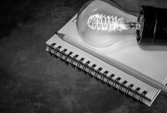 lampadina su un taccuino con la matita, l'ispirazione e l'istruzione Fotografia Stock