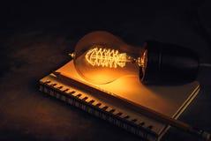 lampadina su un taccuino con la matita, l'ispirazione e l'istruzione Fotografie Stock