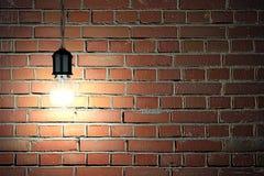 Lampadina sul fondo scuro del muro di mattoni Fotografie Stock