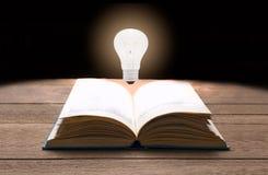 Lampadina sul primo piano del libro aperto su buio Fotografia Stock