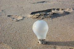 Lampadina sulla sabbia per l'idea, concetto di ispirazione Immagini Stock Libere da Diritti