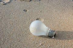 Lampadina sulla sabbia per l'idea, concetto di ispirazione fotografia stock